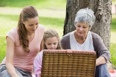 Grandmother mother and daughter with picnic basket at park - stock photo