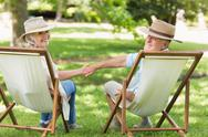 Stock Photo of Relaxed mature couple sitting in deck chairs at park