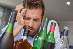 Drunk businessman slumped beside many spirit bottles - stock photo