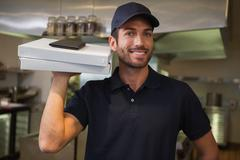 Smiling pizza delivery man holding two pizza boxes - stock photo