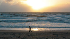 Man walking on the beach with storm waves at sunset - stock footage
