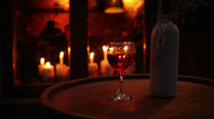 Wine bottle with glass on the wooden barrel cozy bar still life Stock Footage