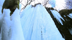 Frozen waterfall water runs down the icicles in slow motion Stock Footage
