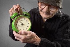 elderly woman holding an alarm clock. - stock photo