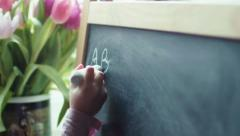 Small girl writing letters abs on a black board Stock Footage