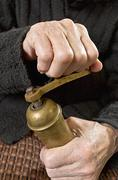 Old woman hands rotate retro coffee grinder. Stock Photos