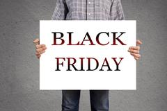 Stock Photo of person holding banner with black friday message.