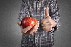 person holding tasty red apple and showing thumb up. - stock photo
