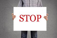 Stock Photo of person holding banner with stop message