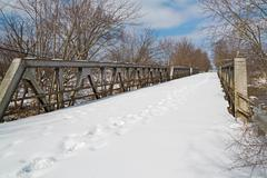 Snowy Footprints on Old Bridge Stock Photos