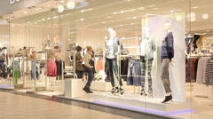 People walk along the clothes storefronts in the shopping mall - stock footage