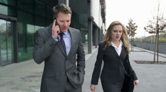 STEADY-CAM Slow-Mo: Business Couple Disputing On Phone While Leaving. Stock Footage