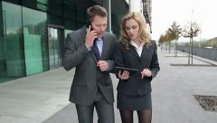 STEADYCAM Slow-Mo: Business Couple Checks Digital Tablet While Talking On Phone. Stock Footage