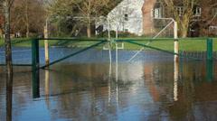 Car splashes past flooded gates Stock Footage