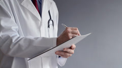 Male doctor is writing RX prescription while standing. - stock footage