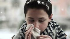 Sick teenage boy sneezing in snowy weather HD Stock Footage