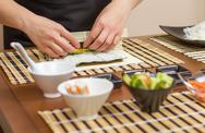 Stock Photo of hands of woman chef rolling up a japanese sushi