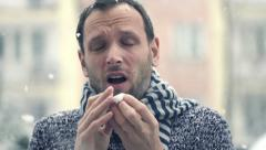 Sick man blowing nose in snowy weather, super slow motion, shot at 240fps HD - stock footage