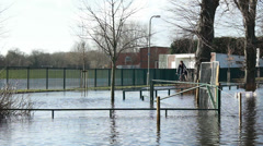 Cyclists passes flooded playing field (UK severe floods) Stock Footage
