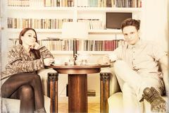 Glamor man and woman sitting on armchairs in the library Stock Photos