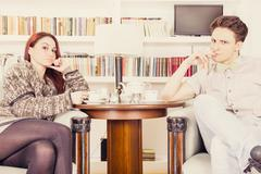 serious glamor couple sitting on armchairs in the library - stock photo