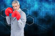 Stock Illustration of Composite image of tough businessman with boxing gloves