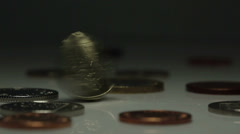 UK One Pound Coin spinning and falling in between other UK coins Stock Footage