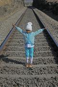 girl standing on railroad track, india - stock photo