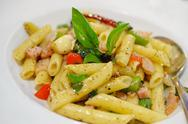 Stock Photo of penne pasta with ham and basil, italian food.