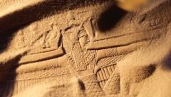 Archaeologist brushes sand from ancient Egyptian carving Stock Footage