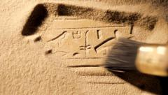Archaeologist brushes sand from ancient Egyptian carving, tracking Stock Footage
