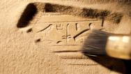 Stock Video Footage of Archaeologist brushes sand from ancient Egyptian carving, tracking
