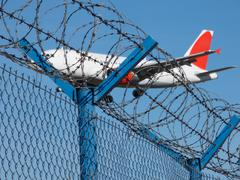 Landing airplane behind barbed wire - stock photo