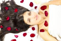 Gorgeous woman laying surrounded by rose petals Stock Photos
