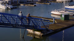 Fisherman Walk onto Docks in Harbor - stock footage