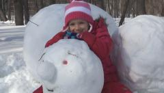 Child Playing with Snowman in Park, Little Girl in Snow, Winter Games Stock Footage