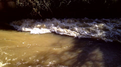 Torrents of flood water gushing through flood relief channel Stock Footage