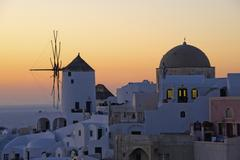 Stock Photo of the historic white washed houses, windmills and domed church of oia town on s