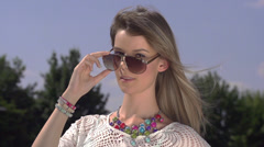 SLOW MOTION: Beautiful woman takes off her sunglasses and winks Stock Footage