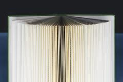 a hard cover printed book, opened and upright. pages fanned out with graduate - stock photo
