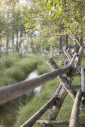 A rural scene, view over a fence made of wooden posts. a small stream. trees Stock Photos