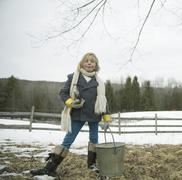 A girl in the snow, carrying a metal bucket. Stock Photos