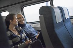 Two people sitting in a railway carriage, smiling. taking a train journey. Stock Photos