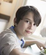A child, a young boy with brown hair and brown eyes sitting at the family tab Stock Photos