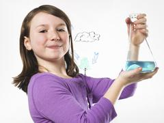 a young girl holding a conical flask of blue liquid in front of an evaporatio - stock photo