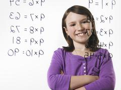 a child looking at a series of multiplication tables written on a see through - stock photo