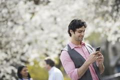 people outdoors in the city in spring time. white blossom on the trees. a you - stock photo