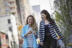 people outdoors in new york city in spring time. two women walking, one check - stock photo