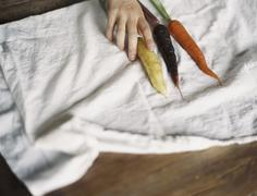 a domestic kitchen table. a person arranging fresh carrots on a white cloth. - stock photo