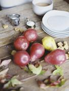 A domestic kitchen tabletop. a small group of fresh organic pears and a stack Stock Photos